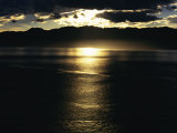 The Sun Casts Golden Rays over the Waters Surface at Twilight Photographic Print by Maria Stenzel