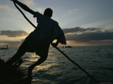 A Fisherman Works the Sails of His Boat as He Heads into the Open Sea Photographic Print by Chris Johns