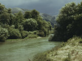 Tree-Lined River Running Through a Mountain Landscape Photographic Print