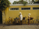Fruit Vendor in a Conical Hat Hangs Ripe and Unripe Bananas on a Bike Photographic Print