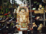 In a Shoe Shop Window, a Chinese Lucky Buddha Offers a Gold Token Photographic Print