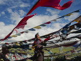 A Tibetan Pilgrim Hoists Prayer Flags Over a Mountain Pass in Tibet Photographic Print by Justin Guariglia