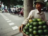 An Orange Vendor Smokes a Cigarette as He Waits for Customers Photographic Print
