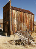 A Wooden Cart Decays in Front of an Abandoned Building Photographic Print by Charles Kogod