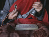 Buddhist Lama with Prayer Book, Prayer Beads and Dorge Photographie par Gordon Wiltsie