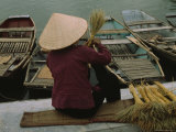 A Woman Makes a Straw Broom as She Awaits Tourists to Ride Her Boat, Hoa Lu Photographic Print