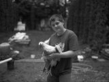 A Young Boy Holds a Chicken in His Backyard in Nebraska Photographic Print by Joel Sartore