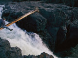 A Man Crosses a Makeshift Bridge over the Roaring Yagtali River Photographic Print by Randy Olson
