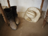 Cowboy Boots and Hat Lie under a Table Photographic Print by Jodi Cobb