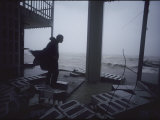 A silhouetted figure observes hurricane wreckage, Photographic Print