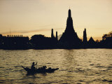A Man Paddles a Boat Past Wat Arun at Twilight Photographic Print by Dean Conger