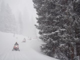 A Small Group of Snowmobilers Turn a Corner in a Snowstorm Photographic Print by Taylor S. Kennedy