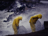 Two Young Boys in Yellow Slickers Play in the Surf Photographic Print by Jodi Cobb