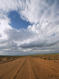 View of Clouds Filling the Sky over a Dirt Road Photographic Print by Richard Nowitz