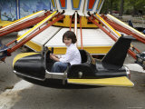 A 6-year-old Girl Rides a Vintage Carnival Ride Photographic Print by Stephen Alvarez