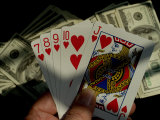 Hand Holding a Straight Flush in Front of Several Hundred Dollar Bills Photographic Print by Todd Gipstein