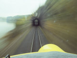 A Trans-Canada Railway Train Rushes Down the Tracks Towards a Tunnel Fotografisk tryk af Paul Chesley