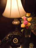Replica of Old Telephone on a Table with a Lamp and a Vase of Roses Photographic Print by Todd Gipstein