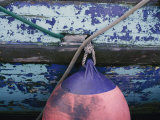 A Colorful Buoy Hangs from Ropes off the Side of a Boat Photographic Print by George F. Mobley