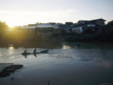 The Sun Sets Behind Waterfront Housing as People Paddle a Canoe Back Home Photographic Print by Steve Raymer