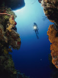 A Diver Swims Between Two Underwater Cliffs Photographic Print by Bill Curtsinger