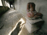 The Headless Statue of a Seated Buddha Sits in a Hallway in a Buddhist Temple Fotografisk tryk af Paul Chesley