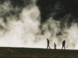 A Silhouetted Family Walks Past a Steaming Hot Springs in the Park Photographic Print by Michael Melford