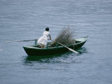 A Person Rows a Boat Full of Branches Photographic Print by Joe Scherschel