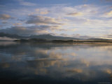 Clouds and Shoreline Reflected in Tranquil Waters at Sunset Photographic Print by Annie Griffiths
