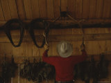 An Outfitter Hangs a Set of Elk Antlers on a Cabin Wall Photographic Print by Raymond Gehman