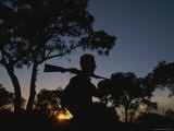 A Silhouetted Man with Rifle Enjoys Sunset at a Private Game Reserve Photographic Print by Tino Soriano