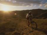 The Sun Sets Behind a Cyclist, out for a Ride on His Mountain Bike Photographic Print by Bobby Model