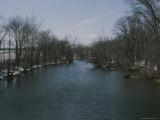 View Looking up River at Banks Covered with Snow and Bare Trees Photographic Print