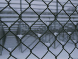 Small Piles of Snow Fill in the Angles of a Chain-Link Fence Photographic Print by Stephen St. John