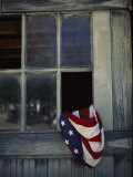 An American Flag Lies Loosely Bunched in an Open Window Fotodruck von Raul Touzon