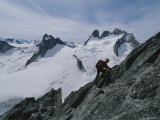 A Climber Ascends Bugaboo Spire with Howser Towers in the Distance Photographic Print by Gordon Wiltsie