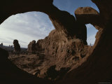 Towering More Than 15 Stories, Double Arch Dwarfs a Park Visitor Fotografisk tryk af Paul Chesley