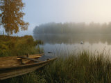 A Weathered Rowboat on the Shore of a Misty Lake Fotografisk tryk af Mattias Klum