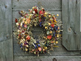 A Delicate Dried Flower Wreath Adorns a Wooden Wall Near a Window Fotografie-Druck von Bill Curtsinger