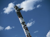 Indian Totem Pole against Blue Sky with Puffy White Clouds Photographic Print by Todd Gipstein