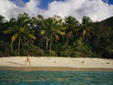 As Palm Trees Sway, a Woman Walks Along a Stretch of White Sand Beach Photographic Print by Raul Touzon