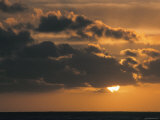 The Sun Sinks to the Sea under a Cloud-Filled Sky at Sunset Photographic Print by Tim Laman