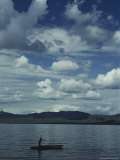 A Man Rows a Boat to Shore under a Cloud-Filled Sky Photographic Print by Bill Curtsinger