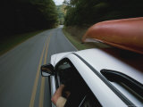 A Car with a Kayak on Top Speeds Down a Two-Lane Highway Photographic Print by Stephen Alvarez