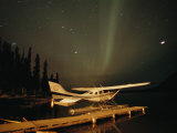 The Aurora Borealis Glows Brightly over a Seaplane Docked on Cli Lake Photographic Print by Raymond Gehman