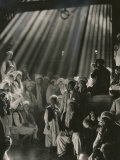 Rays of Sunlight Shine on Men and Boys in a Crowded Warehouse Photographic Print by Maynard Owen Williams