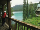 A Woman Looks out on Emerald Lake from an Emerald Lake Lodge Balcony Photographie par Michael Melford