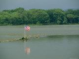 An American Flag Marks a Rock Outcrop Near a Ferry Crossing Photographic Print by Raymond Gehman