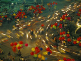 A Blurred View of People Racing Motor Bikes on a City Street at Night Fotografisk tryk af Paul Chesley
