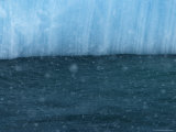 Snow Flakes Drifting Past a Blue Iceberg Photographic Print by Ralph Lee Hopkins